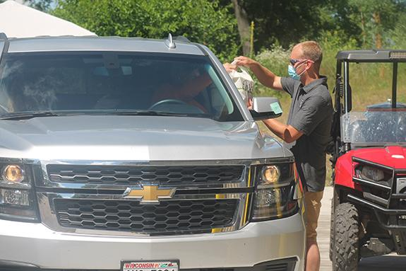 Saxeville-Springwater Fire Chief, Alex Peterson, gives Marv Hazlett some chicken dinners by way of drive-through service during the July 12 chicken barbeque.