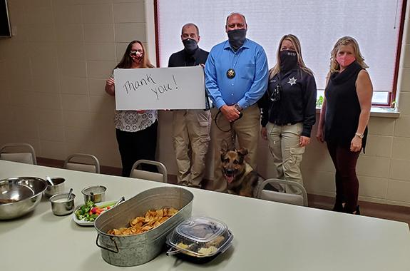 Pictured from left to right are Administrative Professional Darlene Mastricola, Lt. Ryan McElroy, Sheriff Wally Zuehlke and K9 Argo, Dispatcher Kim Gustin, and Medical Examiner Amanda Thoma.