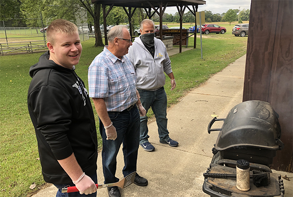 Austin Krueger, his grandfather Gene Krueger, and Neal Krause enjoyed Rally Day with a cook out.