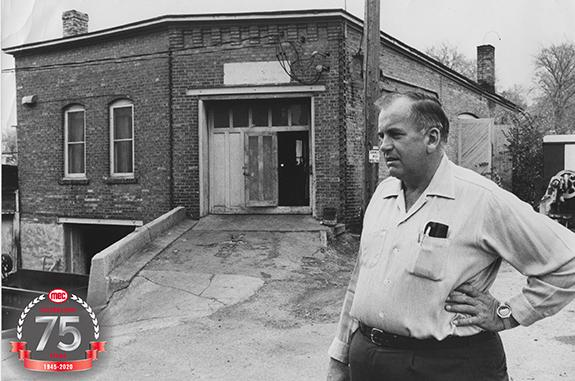 Ted Bachhuber stands in front of the original manufacturing facility.