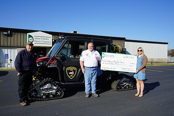 Jeff Myszewski and Mark Piechowski, deputy fire chief, accept the donation from Haley Melby, coordinator at ACEC.